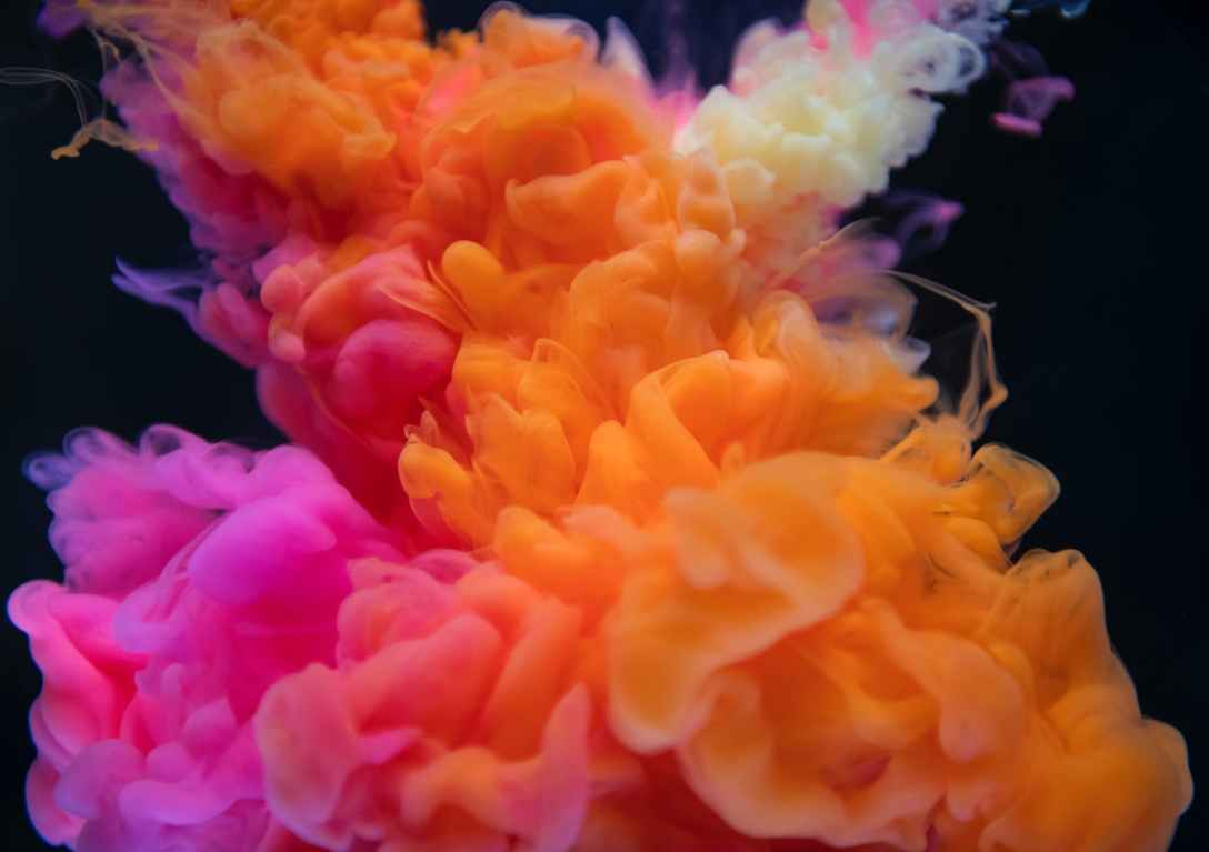 Pink, orange and pale yellow coloured smoke swirl into one another in front of a black background.