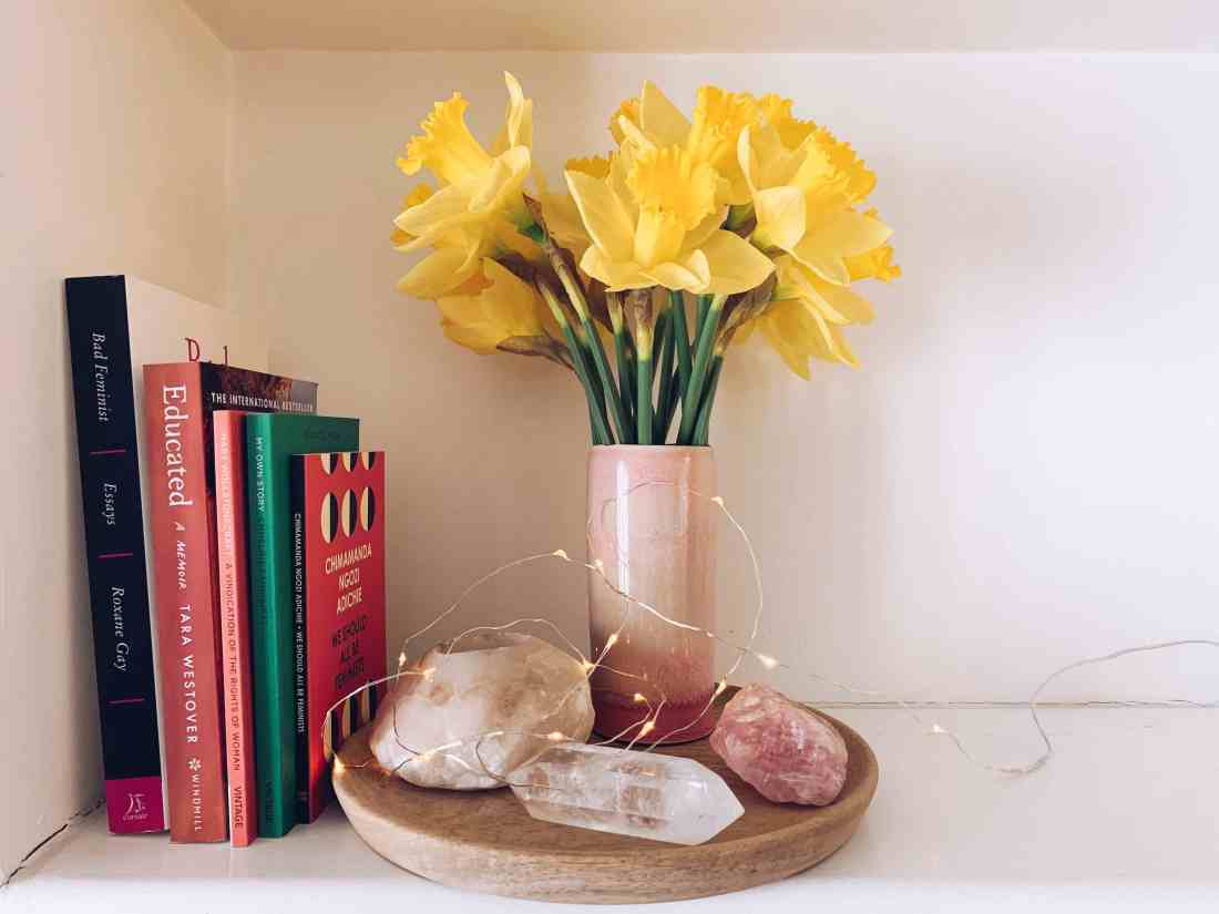 Photograph of bookshelf with five books stacked vertically leaning against the wall. Next to them is a wooden tray holding gemstones, a pink vase with yellow daffodils and a string of fairy lights. The books are Bad feminist by Roxane Gay, Educated by Tara Westover, A vindication of the rights of woman by Mary Wollstonecraft, My own story by Emmeline Pankhurst and We should all be feminists by Chimamanda Ngozi Adichie.