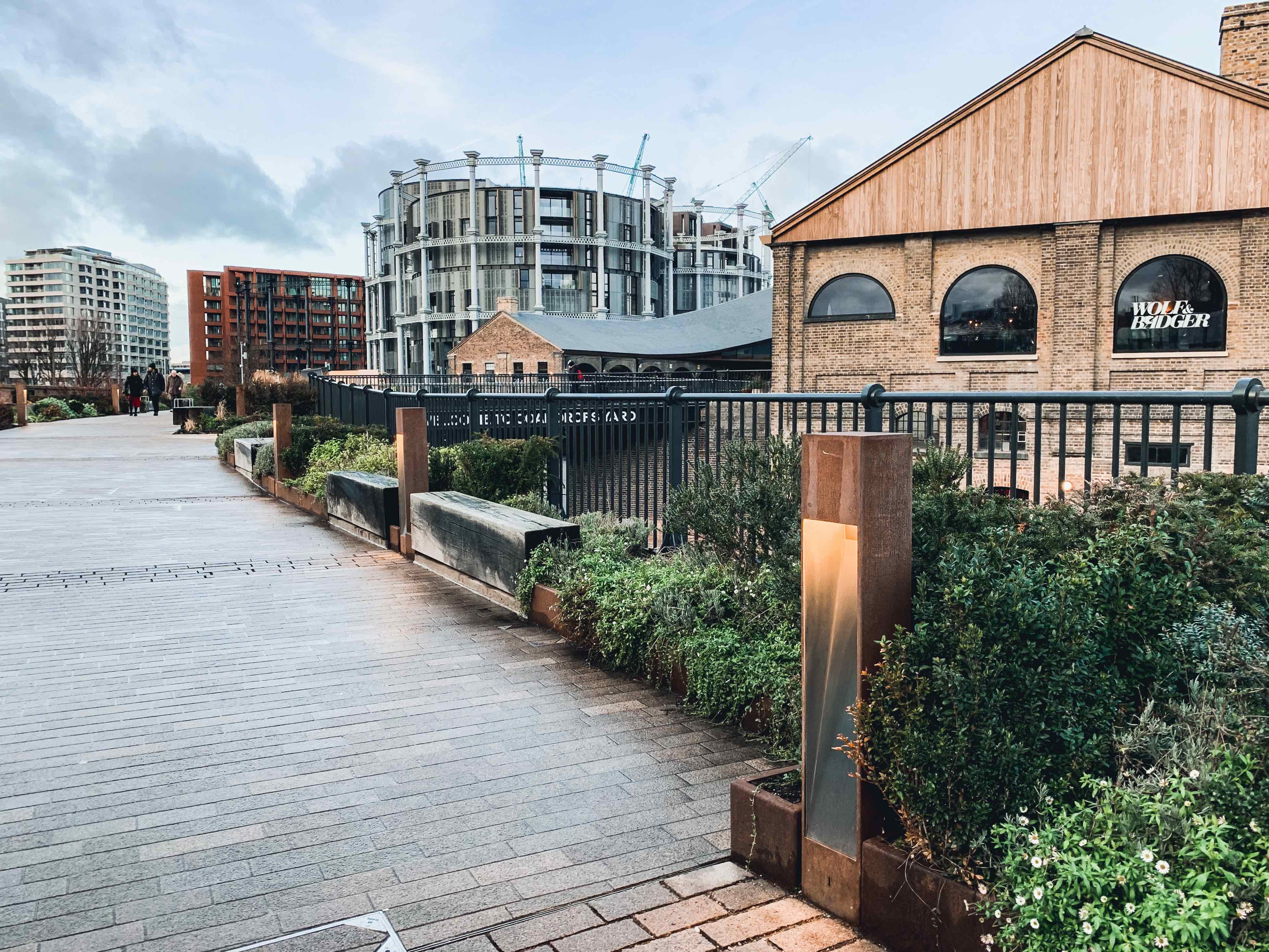 A view of a walkway taking visitors past the Coal Drops Yard to the Gasholders apartment complexes and on along the Regent's Canal Towpath. The vibe is very New York City 'Highline'-esque. The inclusion of vegetation works well with the brick and steel constructions surrounding the place.