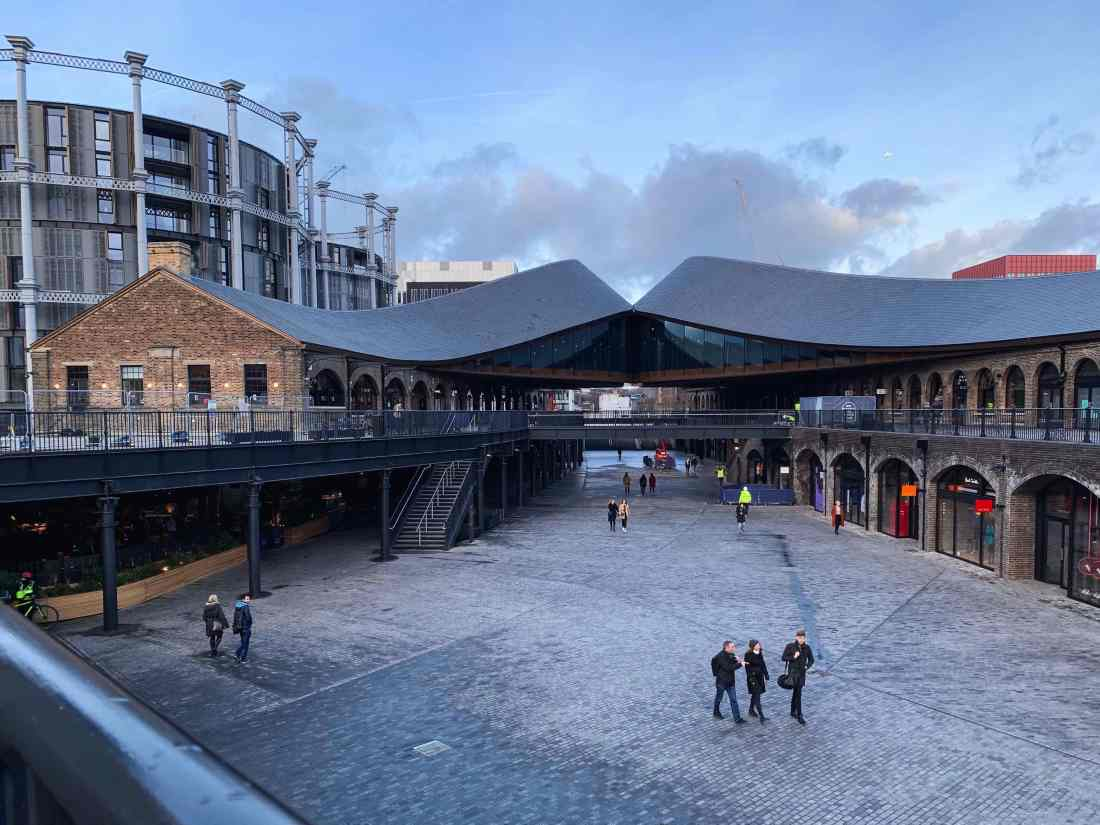 Photograph of the redevelopment of the Coal Drops Yard in London. In view are two old victorian buildings formerly used for storage of produce that came into London on trains. Architect Thomas Heatherwick has created a roof structure that combine the two structures while creating a space between the two buildings by bringing the roofline up between the two buildings in an organic fashion rather than a conventional triangular roof. The shape sort of resemble the shape pages in a book take when its opened in the middle and the pages are held softly at either side.