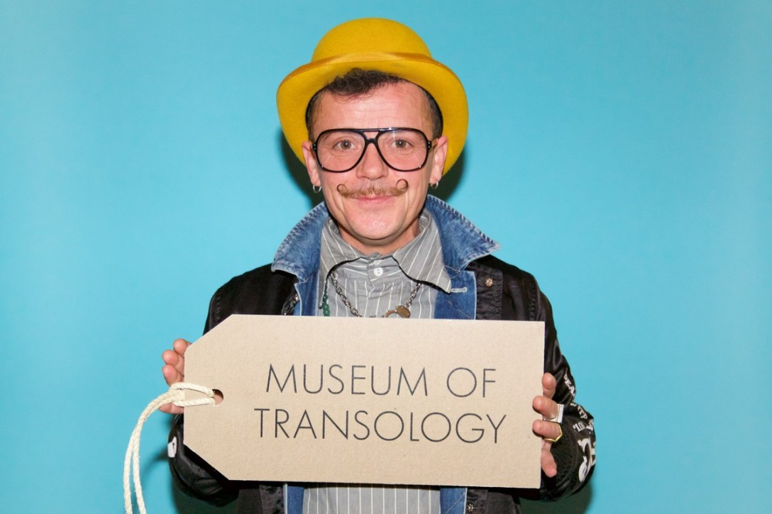 E-J Scott, dress historian, curator, academic and queer cultural producer, holds up the logo for Museum of Transology. The sign is shaped like a paper tag that can be tied to things. On it is written the name of the collection in bold letters.